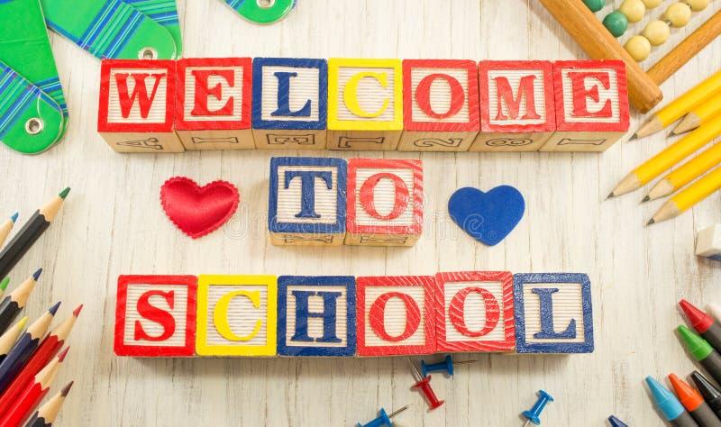 Välkomnande till skolan som är skriftlig i träsovalkovbokstäver royaltyfri foto
