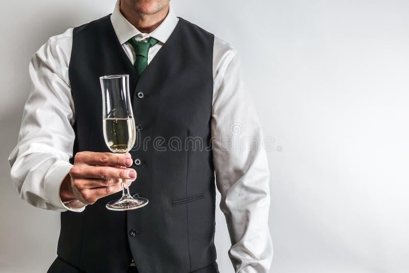 Välla fram den klädda mannen som rymmer ett exponeringsglas av champagne, rostat bröd/bifall arkivfoton