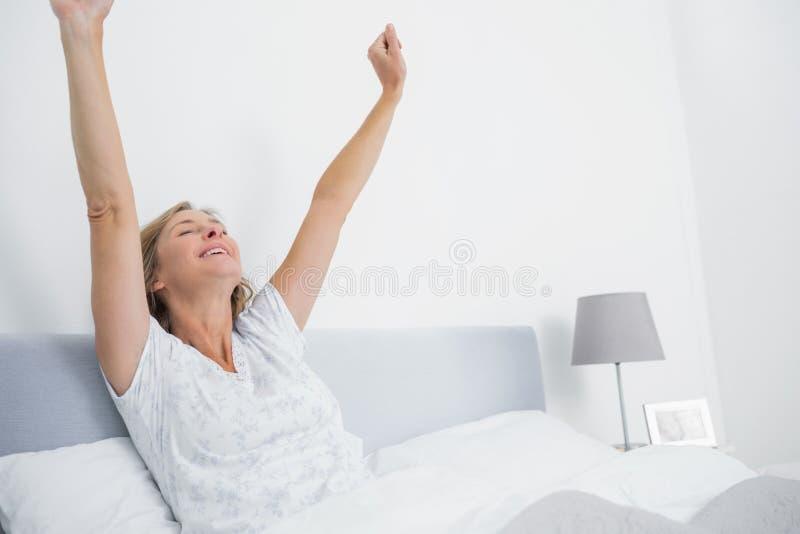 Välla fram den utvilade blonda kvinnan som sträcker, i säng och att le arkivbild