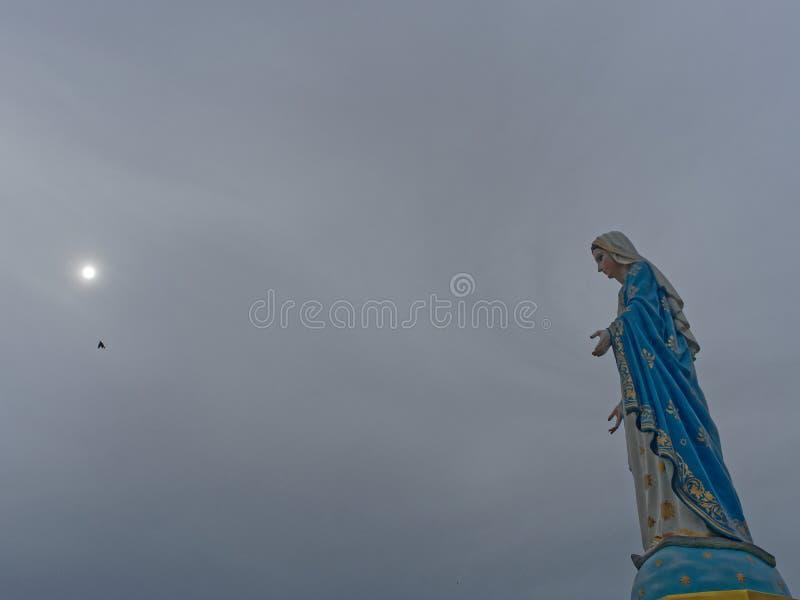 Välsignade jungfruliga Mary, moder av Jesus, staty över mörk himmelbakgrund med solen royaltyfri foto