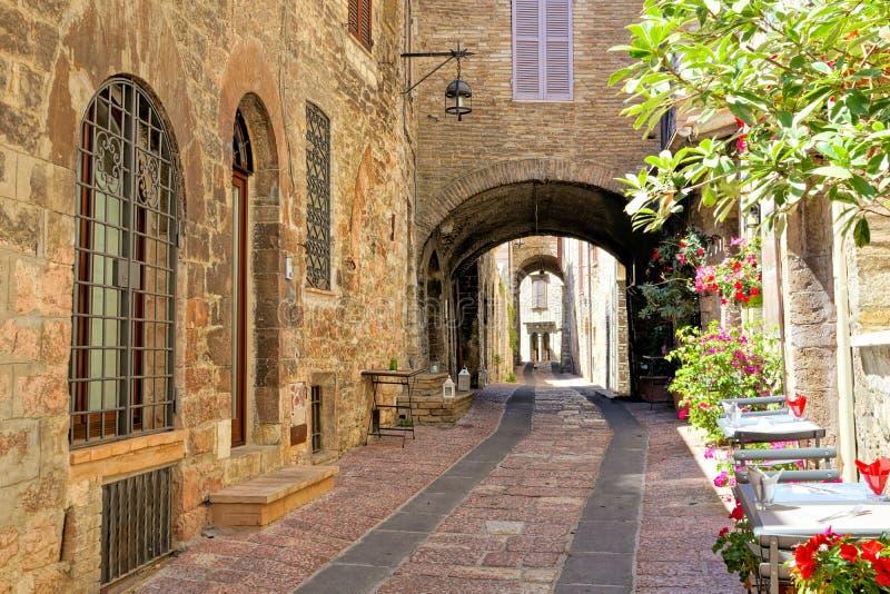 Välva sig gata i den medeltida gamla staden av Assisi med blommor och restaurangtabeller, Italien royaltyfri fotografi