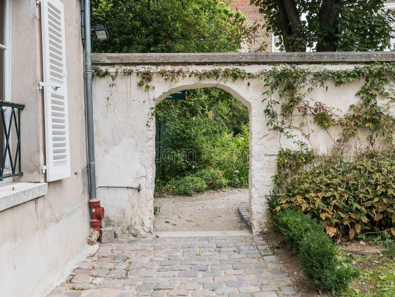 Välvd dörr i trädgårds- vägg på Renoir trädgårdar av Musee de Montmar arkivbilder