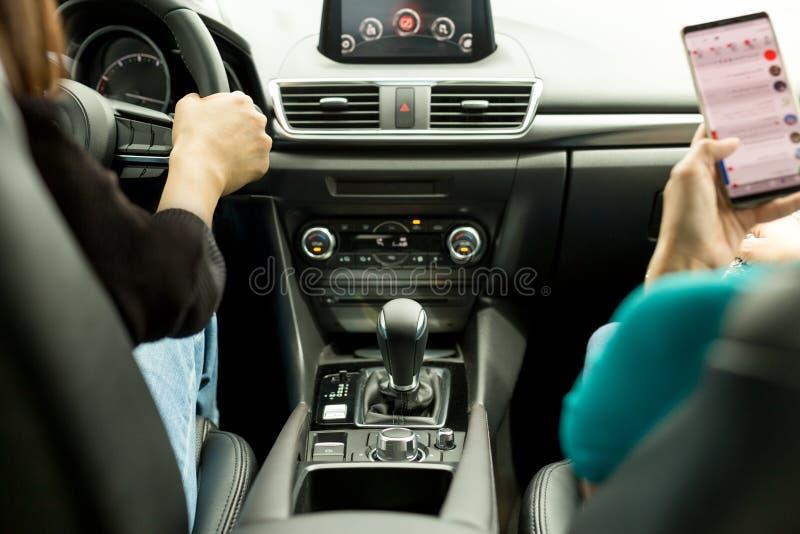 Vän för två kvinna som kör den moderna bilen på landsvägen arkivfoto