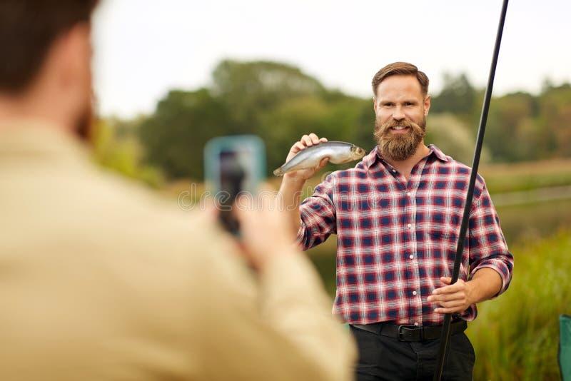 Vän som fotograferar fiskaren med fisken på sjön fotografering för bildbyråer