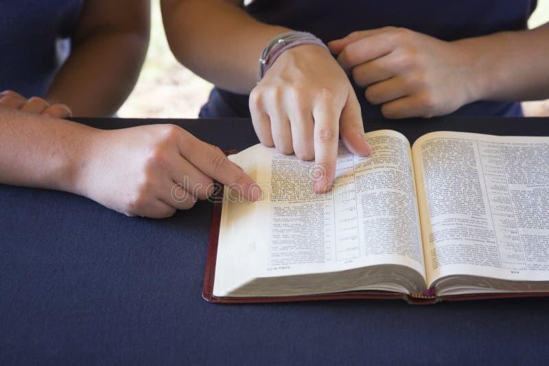 Vän som hjälper någon att studera bibeln arkivfoton