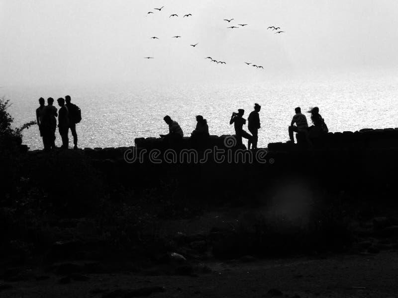 Vän som sitter på fortväggen med havet på bakgrund royaltyfri bild