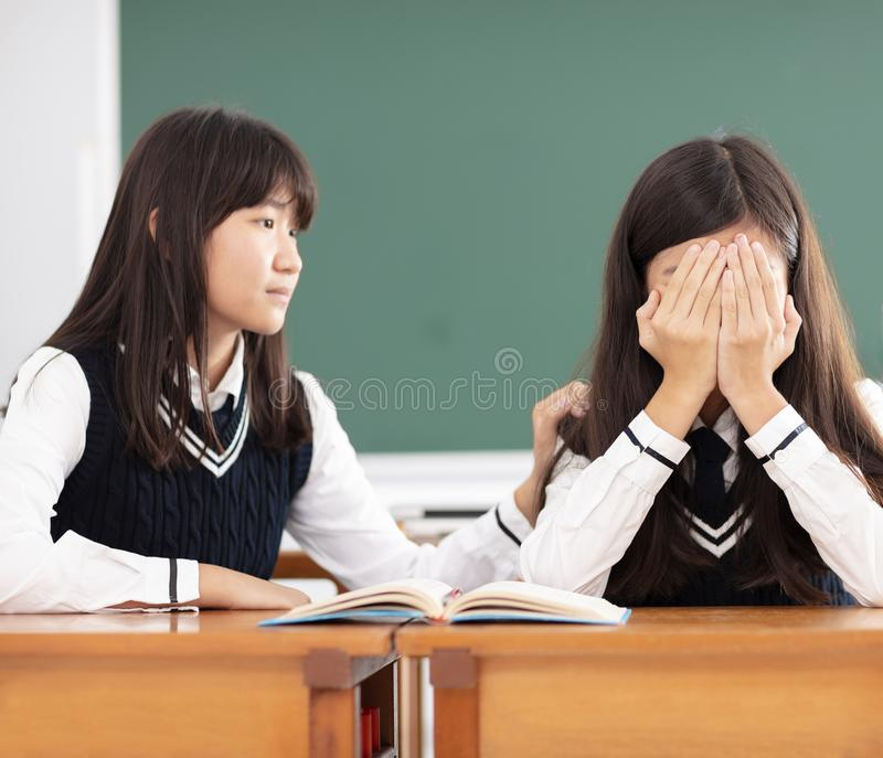 Vän som tröstar till den ledsna studenten i klassrum arkivbilder