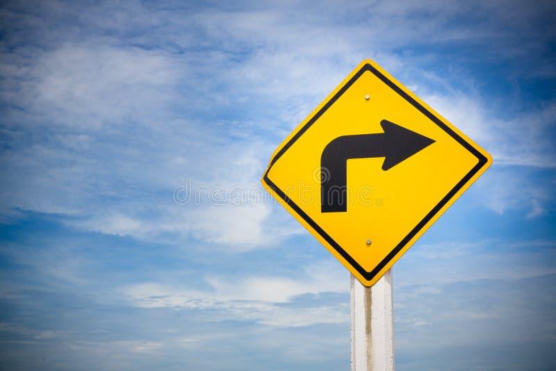 vänd det högra trafiktecknet på gul bakgrund med molnig blå himmel symbol för trans.reglemente arkivbilder