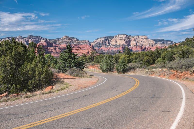 Vänd huvudvägen med sikt av Sedona röd vaggar på bildande i Arizona, USA royaltyfri fotografi