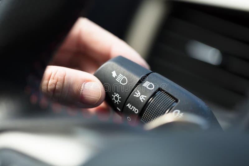 vänd på den ljusa strömbrytaren i bil royaltyfria foton