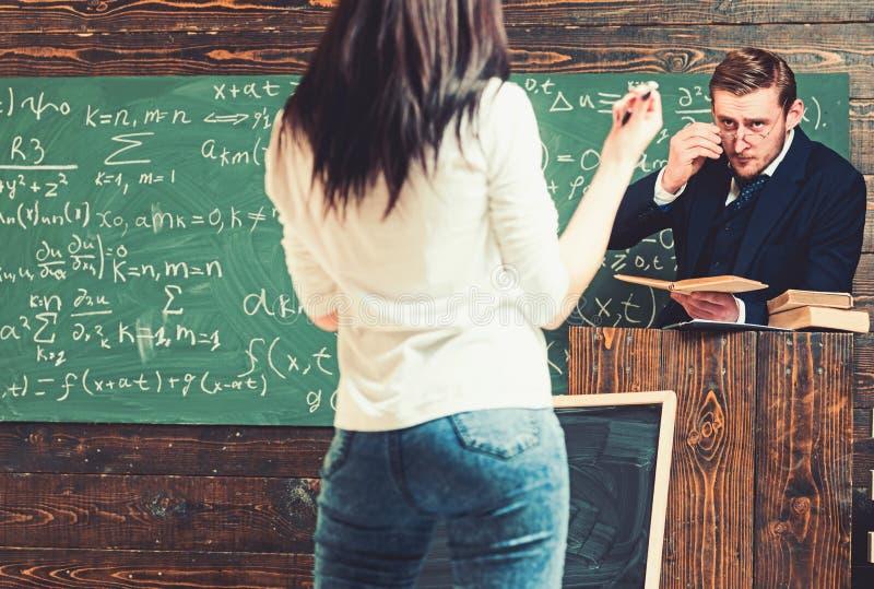 Vänd tillbaka brunettflickan främst av professor Strikt lärare som ser hans kvinnliga student, medan stå på talarstolen arkivbild