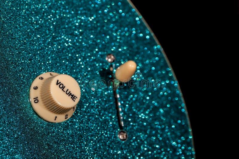 vänd upp volym Kontrollknoppen från en sparkly glam vaggar gitarren royaltyfri bild