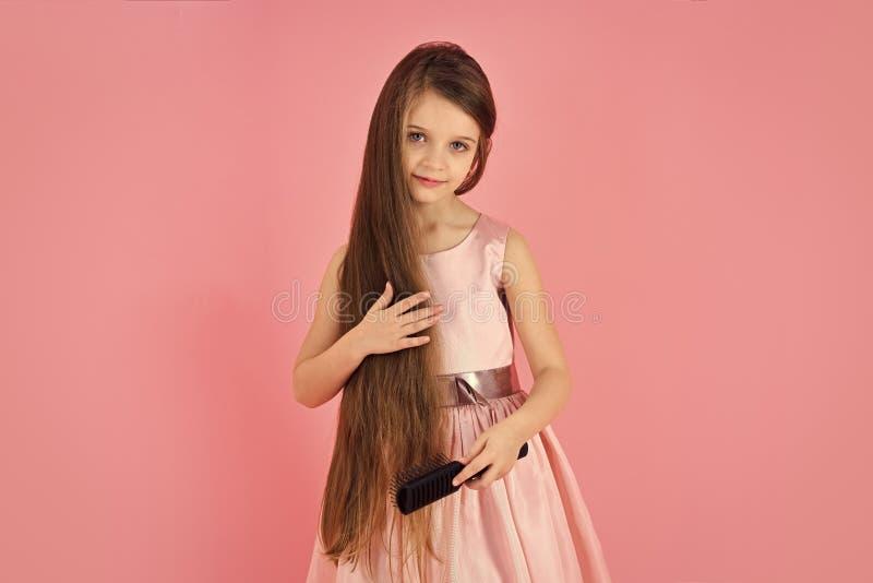 Vända mot den modelilla flickan eller ungen i din webbplats Liten flickaframsidastående i hår för flickabarnborste i innegrej royaltyfri bild