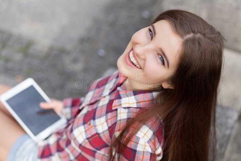 Vända mot ståenden av den unga kvinnan som använder en minnestavlaPC royaltyfri fotografi