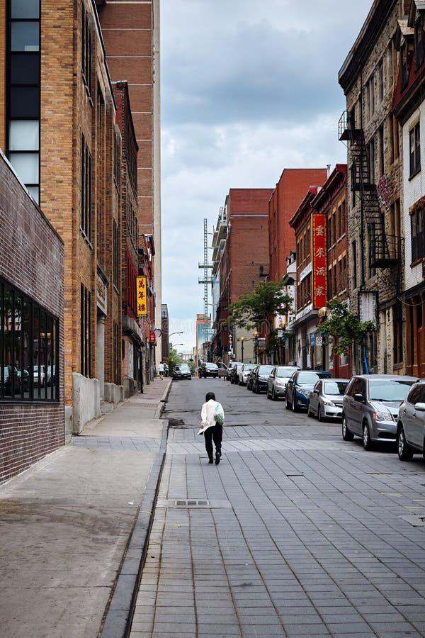 Vända mot tillbaka den asiatiska vuxna kvinnan som går på gatan på en molnig dag i kineskvarter, Montreal, Quebec, Kanada royaltyfri fotografi