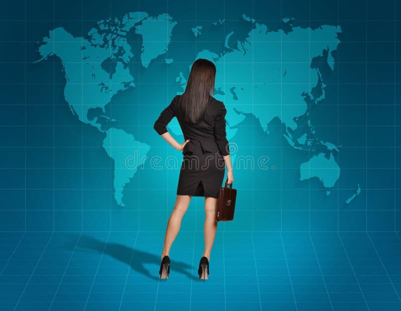 Vända tillbaka blickar för affärskvinna på världskartan royaltyfri bild
