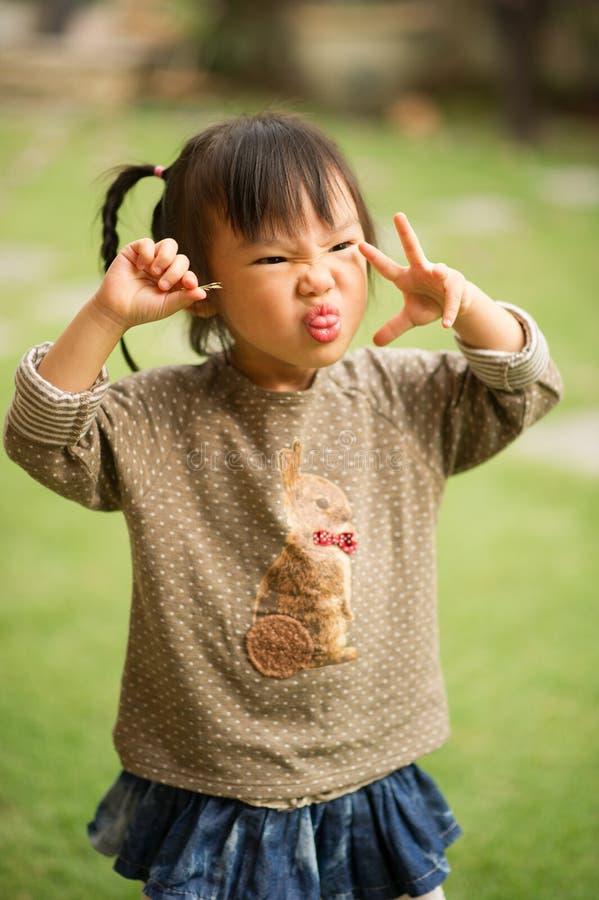 vänder mot årig kinesisk asiatisk flicka 5 i en trädgårds- danande arkivbilder