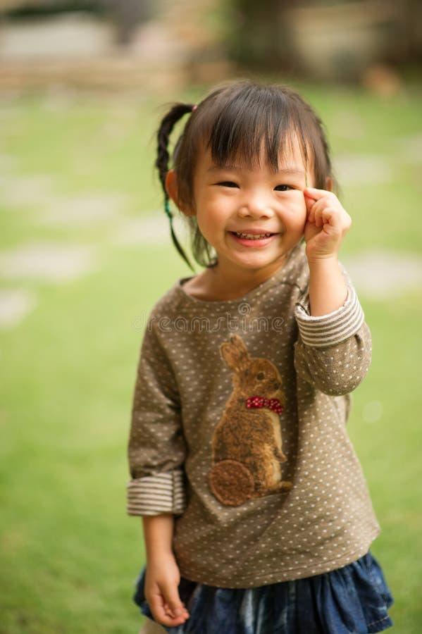 vänder mot årig kinesisk asiatisk flicka 5 i en trädgårds- danande arkivbild