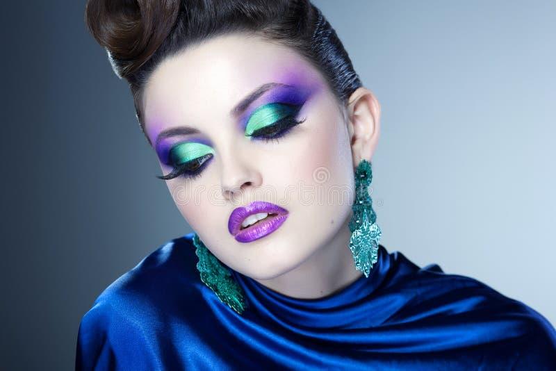 Vänder mot det blåa sminket och frisyren för professionell på härlig kvinna - studioskönhetskottet royaltyfri foto