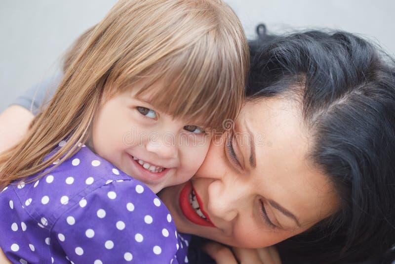 V?nder mot oFaces av modern och dottern som visar sinnesr?relser, medan krama f-moder och dotter som visar sinnesr?relser, medan  royaltyfria foton