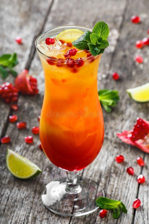 Vändkretscoctail för ny frukt med mintkaramellen, apelsinen och granatäpplet i högväxt exponeringsglas på träbakgrund Sommardrink arkivbilder