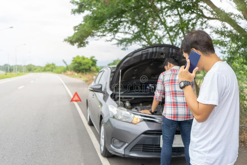 Vänfixandebil som är bruten ner på huvudvägen som kallar för hjälp på mobiltelefonen Två manvänner som talar på telefonen med hjä royaltyfri foto