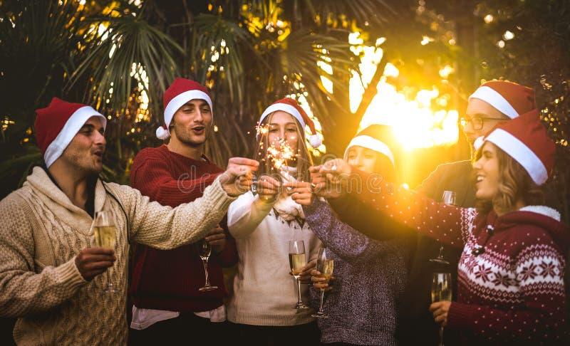 Vängrupp med santa hattar som firar jul med champagne och tomtebloss utomhus arkivbilder