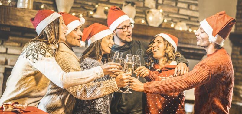 Vängrupp med santa hattar som firar jul med den hemmastadda matställen för champagnevinrostat bröd - begrepp för vinterferier arkivbilder