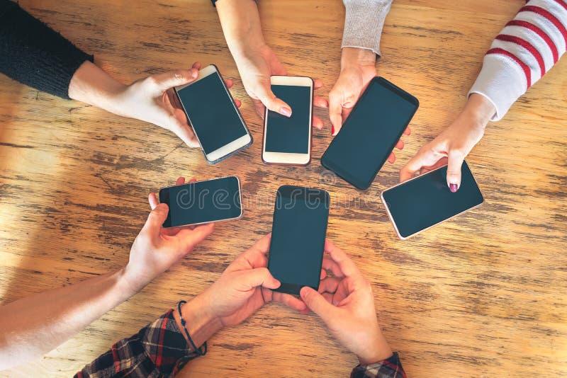 Vängrupp som har gyckel som använder tillsammans smartphones - handdetalj som delar innehållet på socialt nätverk med den mobila  royaltyfri bild