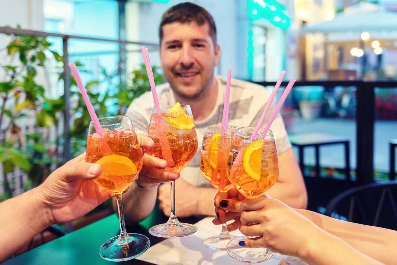 Vänhänder som rostar utsmyckade coctailar, ungdomarsom har gyckel som dricker tillsammans alkohol som är utomhus- på barterrassen arkivbilder