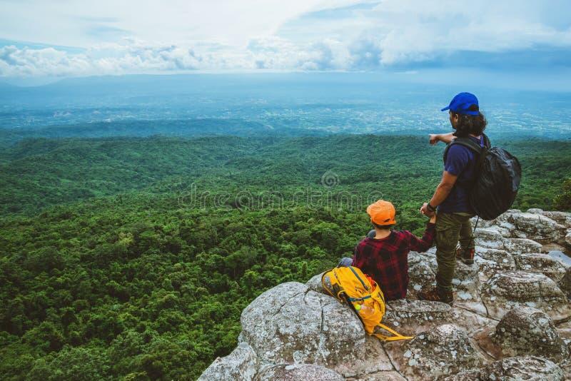 Vänkvinnan och män som asiat reser, kopplar av i ferien Siktsöversikten undersöker bergen royaltyfri bild