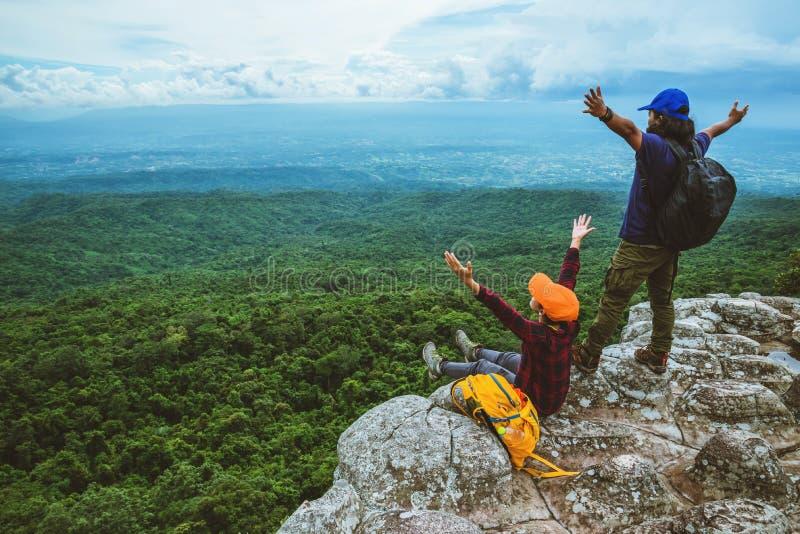 Vänkvinnan och män som asiat reser, kopplar av i ferien Siktsöversikten undersöker bergen royaltyfri foto
