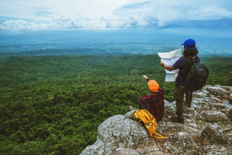 Vänkvinnan och män som asiat reser, kopplar av i ferien Siktsöversikten undersöker bergen arkivfoton