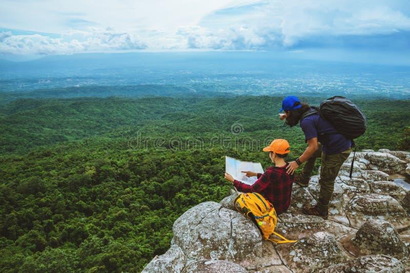 Vänkvinnan och män som asiat reser, kopplar av i ferien Siktsöversikten undersöker bergen fotografering för bildbyråer