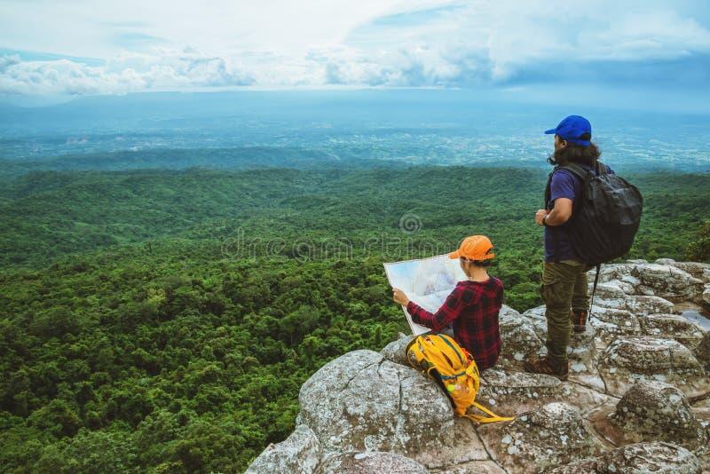 Vänkvinnan och män som asiat reser, kopplar av i ferien Siktsöversikten undersöker bergen royaltyfria bilder