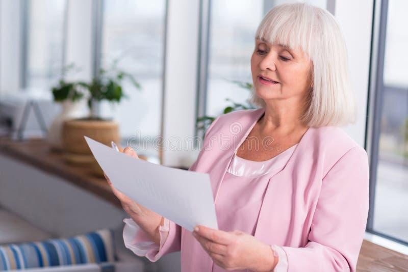 Vänlig äldre dam som konsulterar en källa arkivbilder