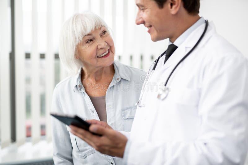 Vänlig åldrig dam som ler, medan se hennes doktor royaltyfria foton