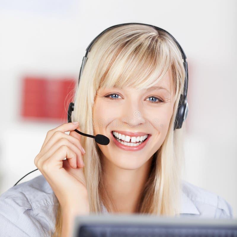 Vänlig affärskvinna som bär en hörlurar med mikrofon royaltyfria foton