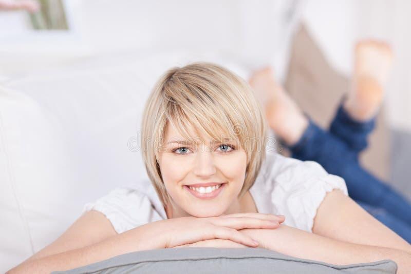 Vänlig blond kvinna som ligger på en soffa royaltyfri fotografi