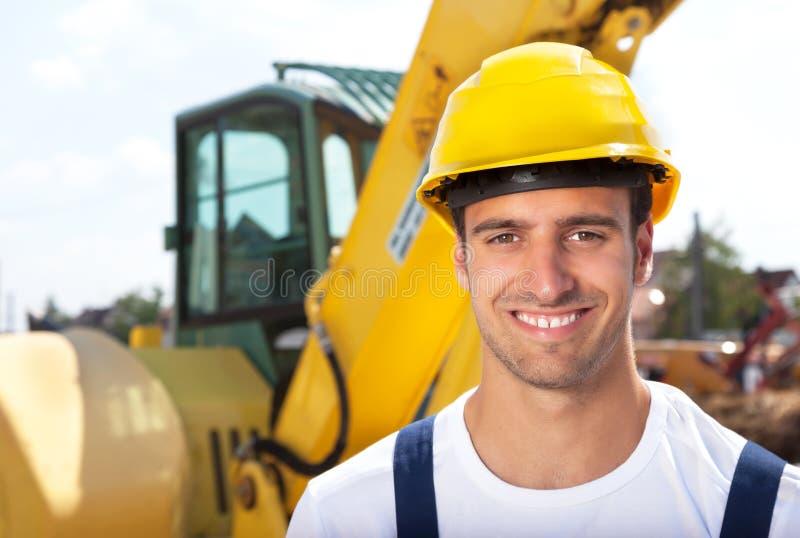 Vänlig byggnadsarbetare framme av hans grävskopa royaltyfri fotografi