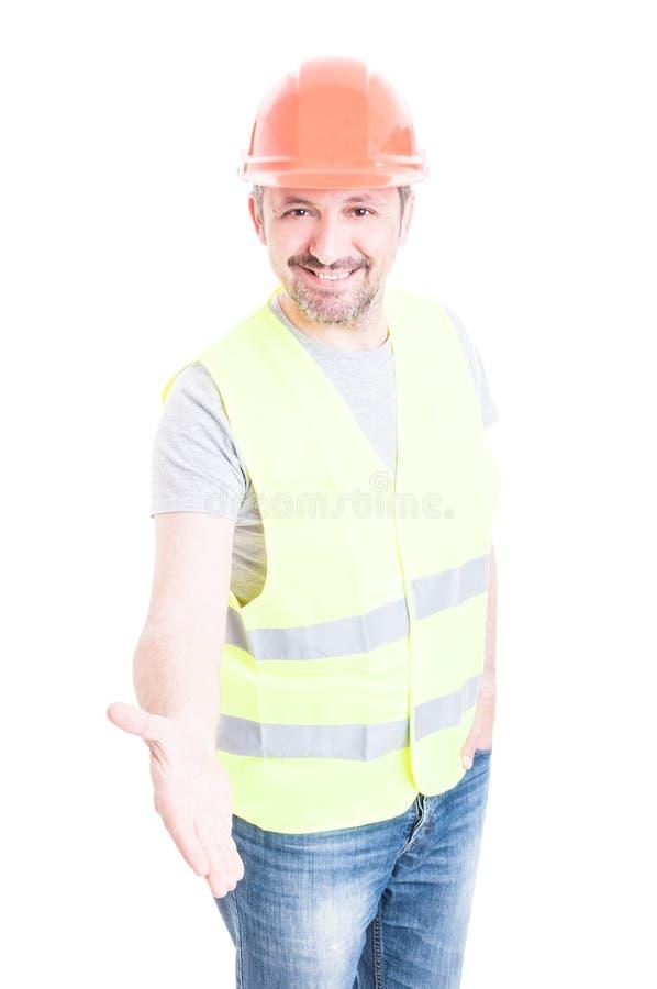 Vänlig byggnadsarbetare som ler och gör en mest gest handskaka arkivbild