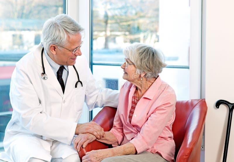 Vänlig doktor som uppmuntrar en äldre kvinna royaltyfria bilder