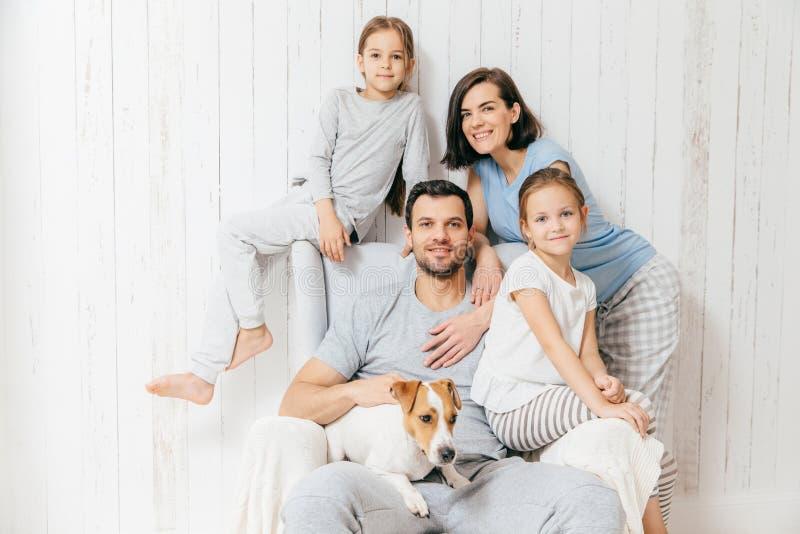 Vänlig familj av fyra memebers: gladlynt europeisk brunett fem arkivfoton
