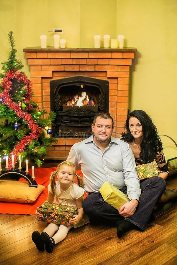 Vänlig familj med en julgran och en spis arkivbilder