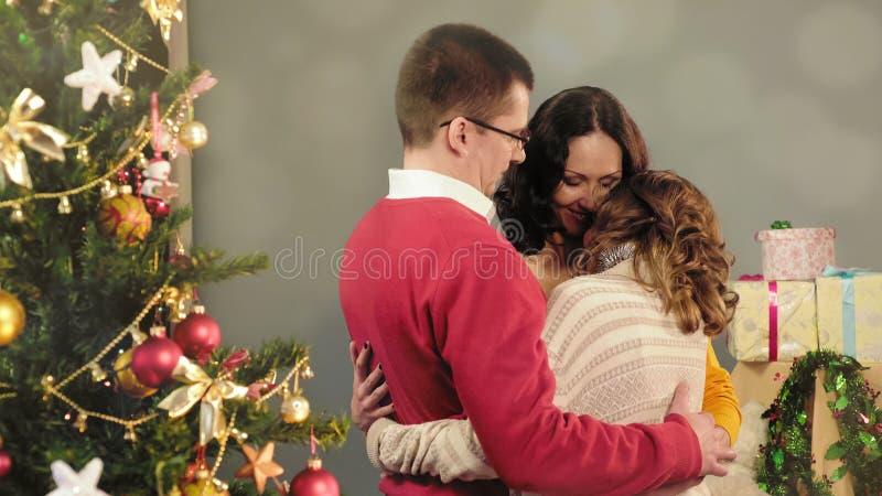 Vänlig familj som kramar och att gratulera sig på ferier, idyll hemma arkivbilder