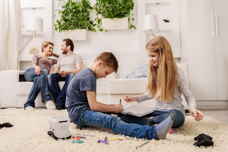 Vänlig familj som underhåller i vardagsrum arkivbilder