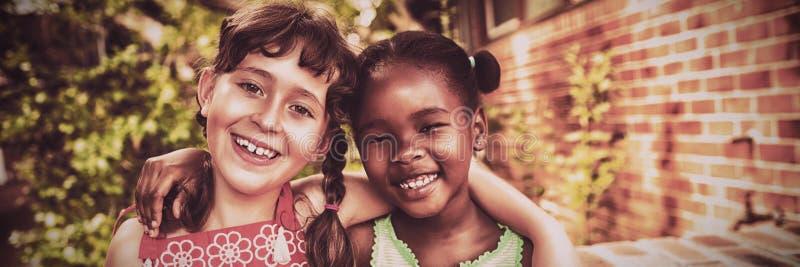 Vänlig flicka som två poserar och ler royaltyfri fotografi