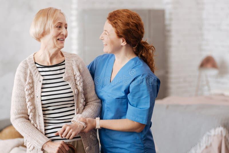Vänlig glad sjuksköterska som tycker om en pratstund med hennes patient royaltyfri fotografi