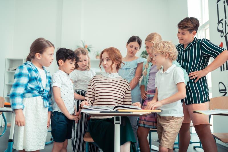 Vänlig grundskolalärare som talar med hennes elever royaltyfri foto