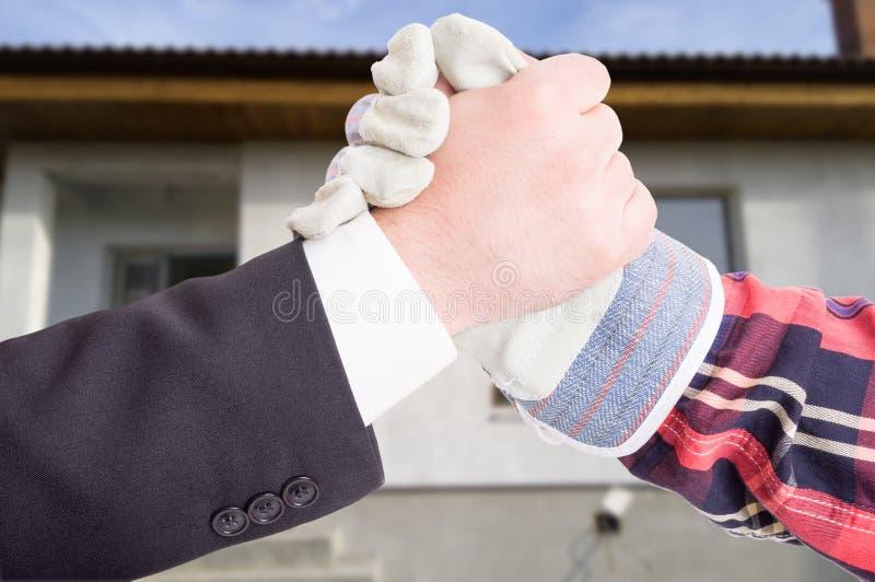 Vänlig handskakning mellan affärsmannen och teknikern royaltyfri bild